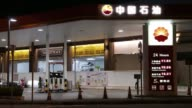 The PetroChina Co logo stands illuminated at one of the company's gas stations at night in Hong Kong China on Monday Aug 21 Traffic drive past an...