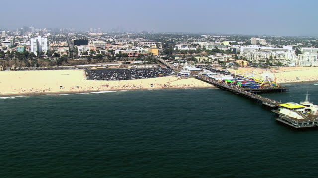 AERIAL The Pier and a pristine beach with the city beyond / Santa Monica, California, United States