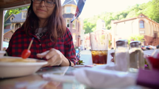 The pretty 16 years old teenager girl eating in the street cafee in Jim Thorpe, Poconos region, Pennsylvania