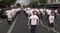 The Pride of Ardoyne Flute Band, a loyalist/unionist marching band, approaches a typically Catholic area of Belfast, Northern Ireland.