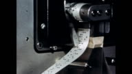 CU of the punched tape begin read by translation machine / CU of officer feeding the translation into the machine / CU paper that reads THIS IS THE...