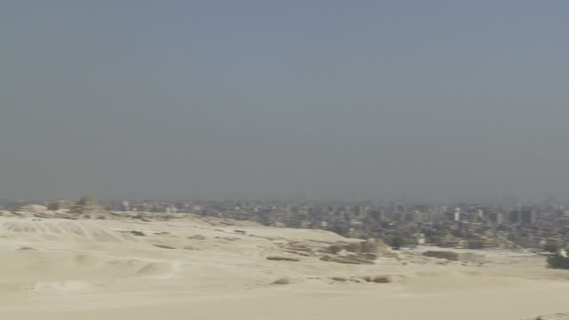 The pyramids of the Giza Necropolis tower above the city of Cairo. Available in HD.