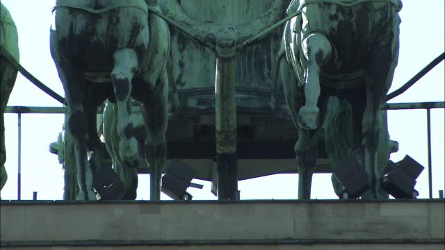 The Quadriga Statue depicts horses pulling a chariot.