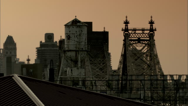 The Queensboro Bridge and high-rise buildings contrast with an orange sky. Available in HD.