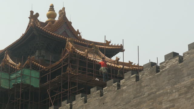 The renovation of ancient buildings has never stopped in Beijing and it costs a lot of money now they are repairing the watch tower Migrant workers...