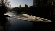 The River Avon cascades down a series of wiers near the Pulteney Bridge in Bath, England. Available in HD.