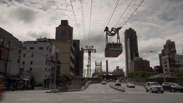 The Roosevelt Island Tram comes into the station in Manhattan. Cars travel under as they come off of the Queensboro Bridge The aerial tramway spans the east river from Roosevelt Island to Manhattan.
