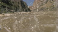 The rough waters of the Colorado River surge under a raft. Available in HD.