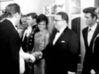 London INT Queen Elizabeth II enters with Bernard Delfont and shakes hands Black attendant boy Queen shakes hands with Harry Secombe Side view Queen...