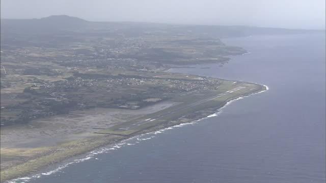 The runway of Tokunoshima Airport stretches along the coast of Tokunoshima Island, Japan.
