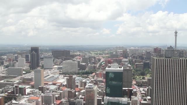 The Sentech Tower stands on the city skyline as traffic passes along a road bridge across railway tracks seen from the Carlton Center in Johannesburg...