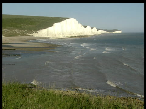 The Seven Sisters Cliffs high and white above sea with gentle waves below.