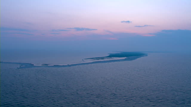 The sky glows behind an island off the coast of Mississippi.