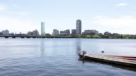 The skyline of downtown Boston Massachusetts can be seen from across the Charles River as kayakers rowers and sailboats pass by Shots of boats...