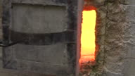 The small door to a large furnace is opened by hand and a blowpipe poked inside, UK.