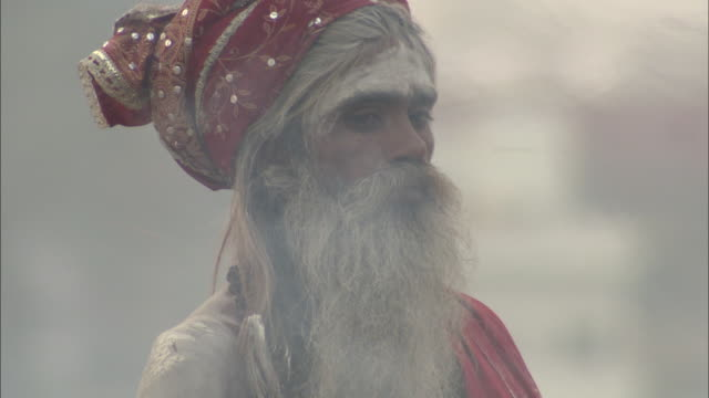 The smoke of a cremation ceremony drifts past a heavily bearded man who wears a scarf on his head.