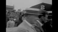 'The Spirit of St Louis' slows as it lands on airfield in Hartford CT / aviator Charles Lindbergh smiles as he shakes hands while in an open car with...