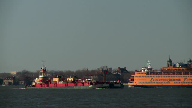 The Staten Island Ferry passes a fuel barge on the Hudson River.
