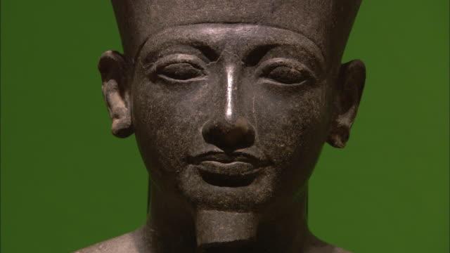 The statue of a pharaoh contrasts against a green background in Luxor.