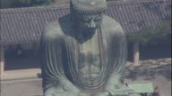 The statue of  Kamakura Daibutsu presides over a temple courtyard.