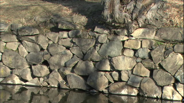 The stone moat walls at Matsumoto Castle reflect in the waters.