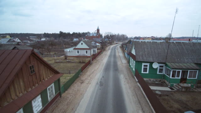 The street in the small town in the Ivyanets going to the catholic cathedral of the Saint Aliaksey, XIX-XX centuries, Belarus, Eastern Europe. Aerial drone footage.