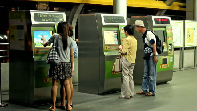 The subway, ticket machine, time lapse of people are waiting.