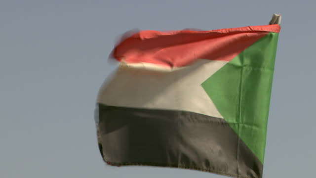 The Sudanese flag flies from a flagpole.