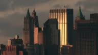 The sun breaks through a series of skyscrapers in lower Manhattan.  Clouds rush behind