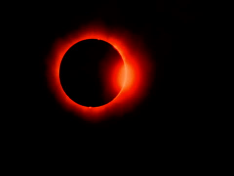 The sun emerges from behind the moon after a solar eclipse.