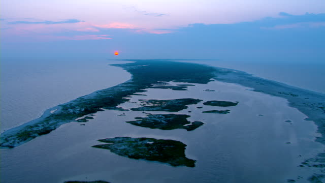 The sun glows behind an island off the coast of Mississippi.