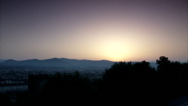 The sun glows behind the Apennines near the city of Florence. Available in HD.