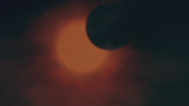 The sun glows orange against the moon's silhouette in a partial solar eclipse.