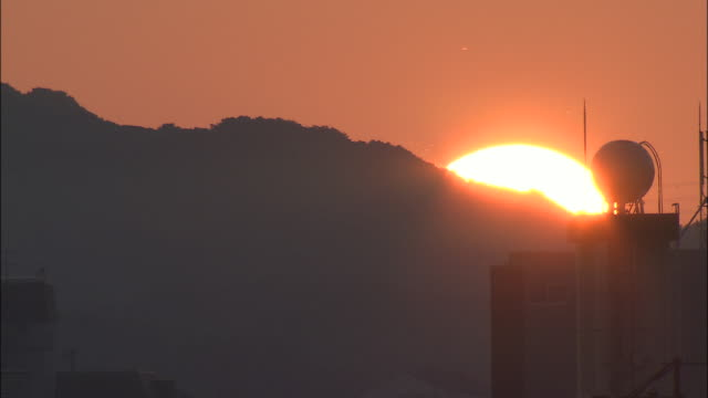 The sun gradually setting behind silhouetted mountain ridge, Japan