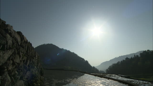 The sun has risen over the rice terrace: Long shot/ Pan left/ Stone walls: Medium shot