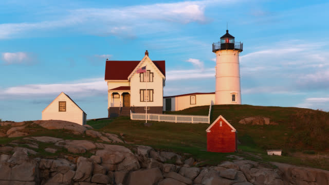 T/L The sun is setting on Cape Neddick Lighthouse also known as Nubble Light / York, Maine, USA
