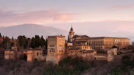 T/L The sun is setting on the Alhambra and the Sierra Nevada mountain range viewed from the Mirador de San Nicolás in the Albaycin of Granada / Granada, Spain