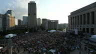 The sun sets as a crowd grows during an outdoor concert in downtown Nashville, Tennessee.