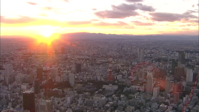 The sun sets over Tokyo's skyline with the Tokyo Tower.