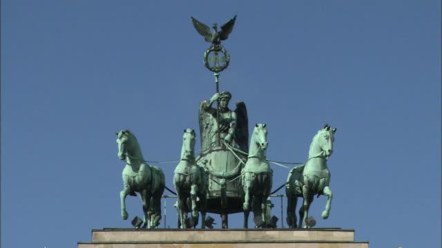 The sun shines on the Quadriga Statue on the Brandenburg Gate.