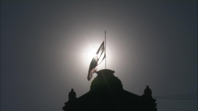 The sun shines through a flag on a dome.