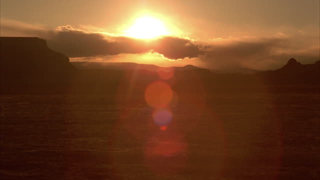 The sun sinks below a desert horizon.