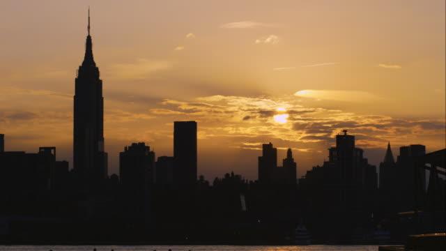 The sunrises over a a golden sky and the the Manhattan Skyline