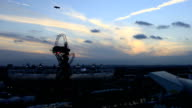 The sunsets during the Closing Ceremony over the London 2012 Olympic Park as the Stadium and Aquatics Centre are lit up The sun sets behind the...