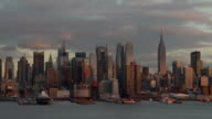 The sunsets on Manhattan and the skyline turns a golden color.  Clouds rush by.