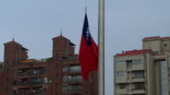 The Taiwanese flag being lowered by a soldier in Taipei