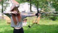 The teenager girl shooting a bow, practicing archery at the backyard