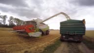 The threshing machine of a combine harvester passes through a field of tobak winter wheat as it is harvested by a combine harvester manufactured by...