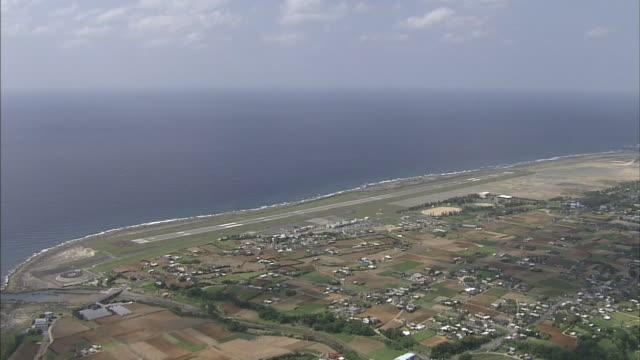The Tokunoshima Airport runway stretches along the coast of  Tokunoshima Island, Japan.