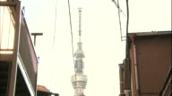 The Tokyo Skytree towers above an alley in a neighborhood.